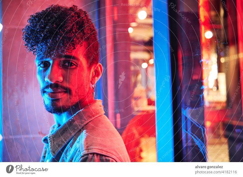 junger hispanischer Mann in der Nähe eines Neonlichts mit blauen und roten Lichtern neonfarbig männlich Model Erwachsener Menschen Person Porträt Typ Gesicht