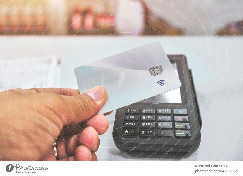 Nahaufnahme eines nicht erkennbaren Kunden, der eine kontaktlose Zahlung vornimmt Kreditkarte Laden bezahlen kaufen Banking arbeiten Drahtlos Rechnung