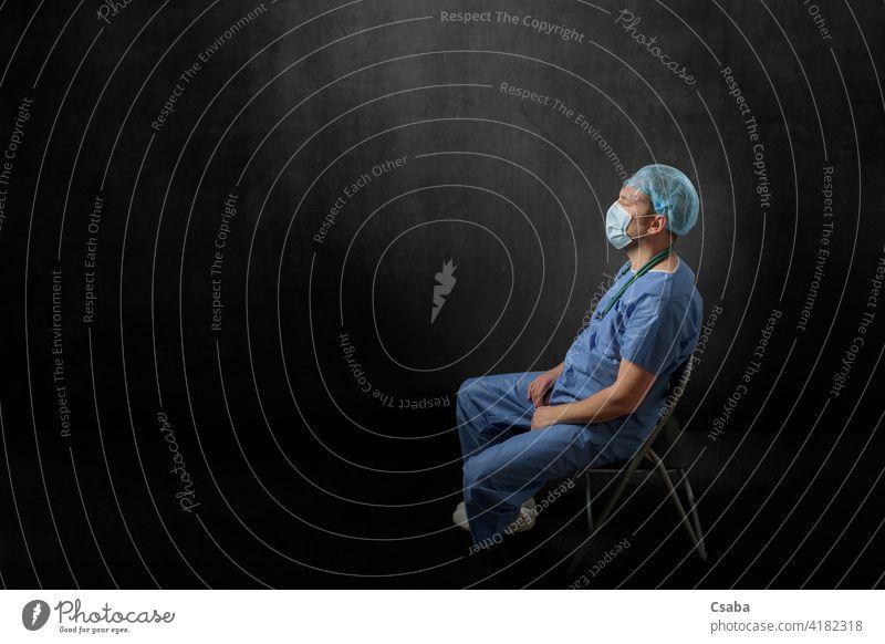 Trauriger, erschöpfter Arzt sitzt in einem dunklen Raum traurig müde Mann Seitenansicht Sitzen enttäuscht Auge zugeklappt Pandemie männlich Stress medizinisch
