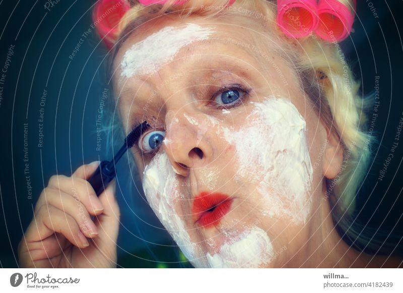 Lippenstift und Wimperntusch schminken Schönheitswahn lustig witzig Ironie Mascara Creme Lockenwickler geschminkt Gesicht Schminke Kosmetik Frau Porträt crazy