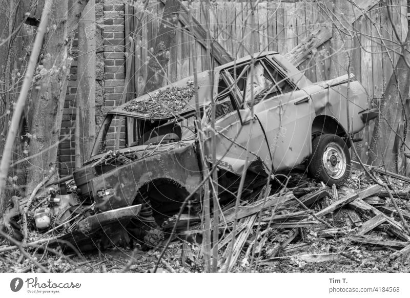 ein kaputter Wartburg liegt vor einer Einfahrt Dorf Unfall Auto car bnw PKW Verkehrsunfall Totalschaden Schrott Außenaufnahme Schaden Menschenleer Fahrzeug