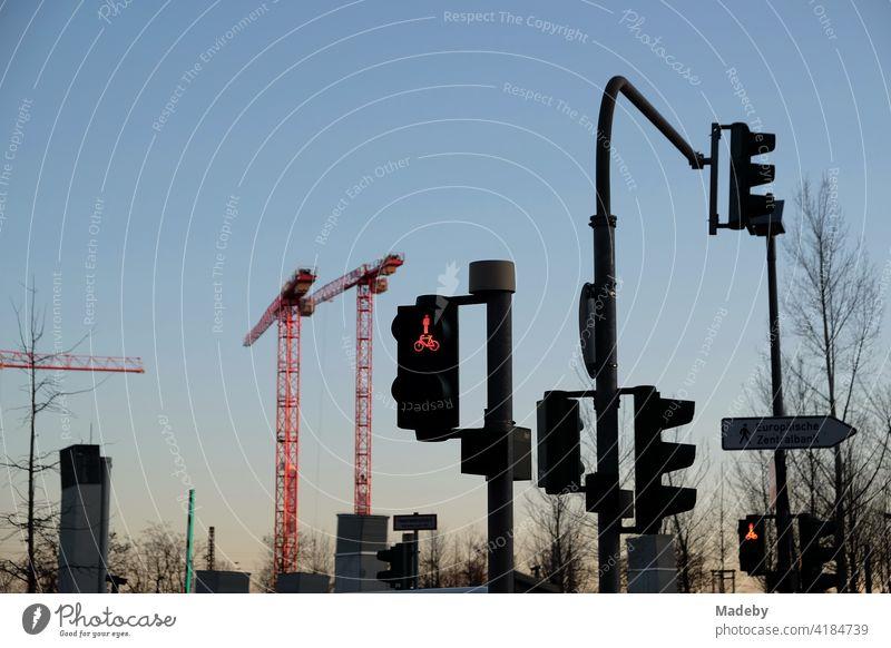 Ampelanlagen und Baukräne im Licht der untergehenden Sonne an der Hanauer Landstraße im Ostend von Frankfurt am Main in Hessen Straße Straßenverkehr Verkehr
