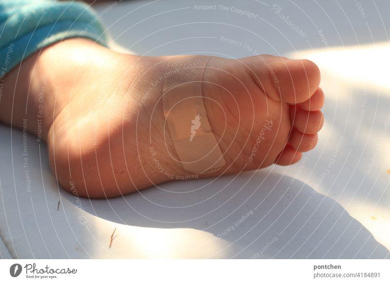 ein Fuß mit Pflaster liegt in der Sonne. Kleinkind- Verletzung und Heilung pflaster verletzung trost heilung fuß kleinkind behüten schutz fürsorge kindswohl
