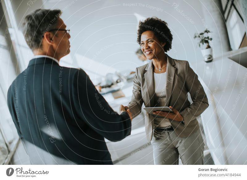Geschäftsfrau hält digitale Tablette und Blick auf gut aussehende Kollegen beim Händeschütteln im Büro Glück Lächeln Exekutive Arbeiter Geschäftsmann ethnisch