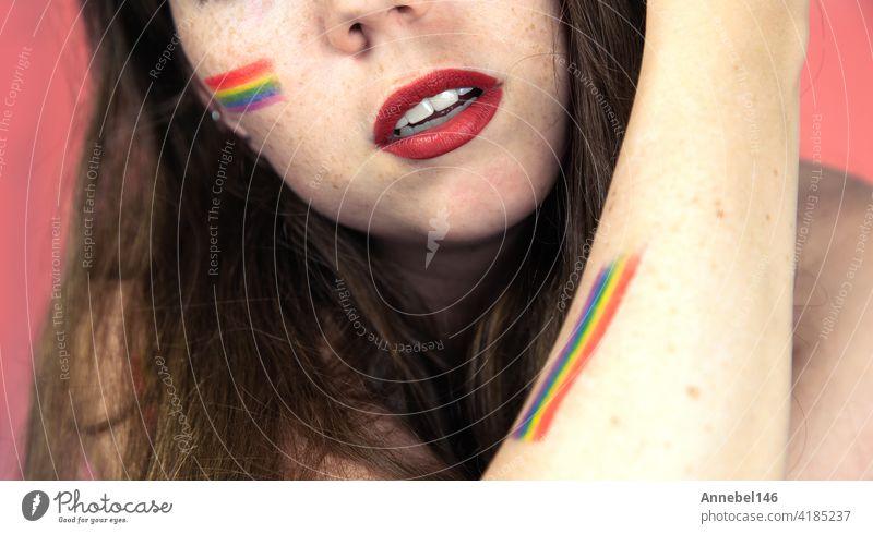 Porträt einer jungen Frau mit Regenbogen Flagge auf Wange und Körper, die LGBT-Gemeinschaft auf einem bunten rosa Hintergrund Mode Hand Pastell Liebe Person