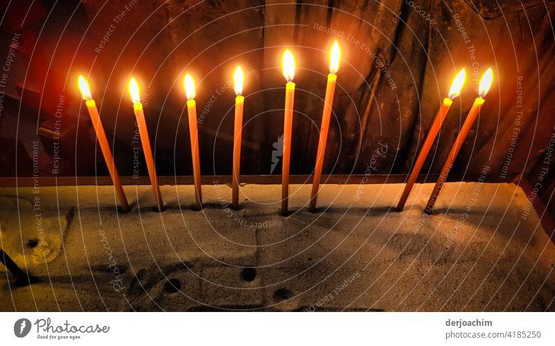 Acht brennende Kerzen in den Sand gesteckt. Flamme Hitze Feuer verrotten Farbfoto orange Wärme Licht heiß Glut gelb Menschenleer Nacht glühen gefährlich