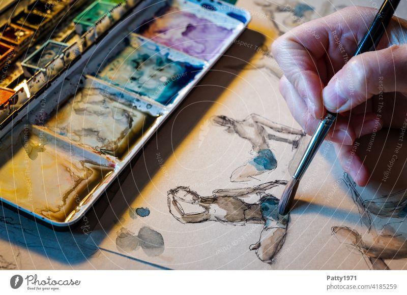 Detailaufnahme eines Wasserfarbkastens und einer Hand die mit Aquarellfarben abstrakte menschliche Figuren skizziert malen Kunst Wasserfarbe Pinsel Kreativität