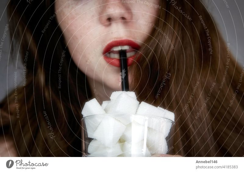 Porträt einer jungen Frau, die mit einem schwarz gefärbten Strohhalm aus einem mit Zuckerwürfeln gefüllten Glas trinkt Junk Food, ungesunde Ernährung, zu viel Zucker in Getränken, Ernährungskonzept