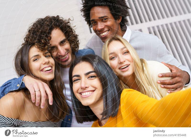 Multi-ethnische Gruppe von Freunden, die zusammen ein Selfie machen, während sie Spaß im Freien haben. Menschengruppe Smartphone rassenübergreifend