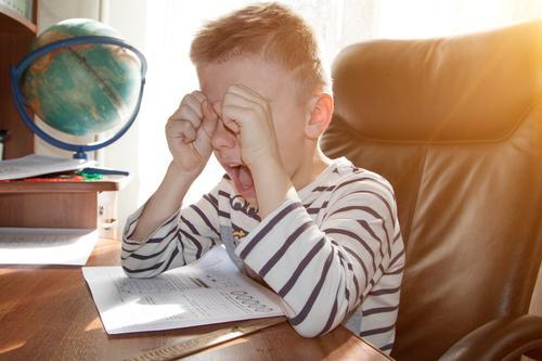 """ein schulpflichtiger Junge, der bei den Hausaufgaben weint und schreit. das Konzept der """"heavy pressure education Schule heimwärts Kind Schüler wütend Stress"""