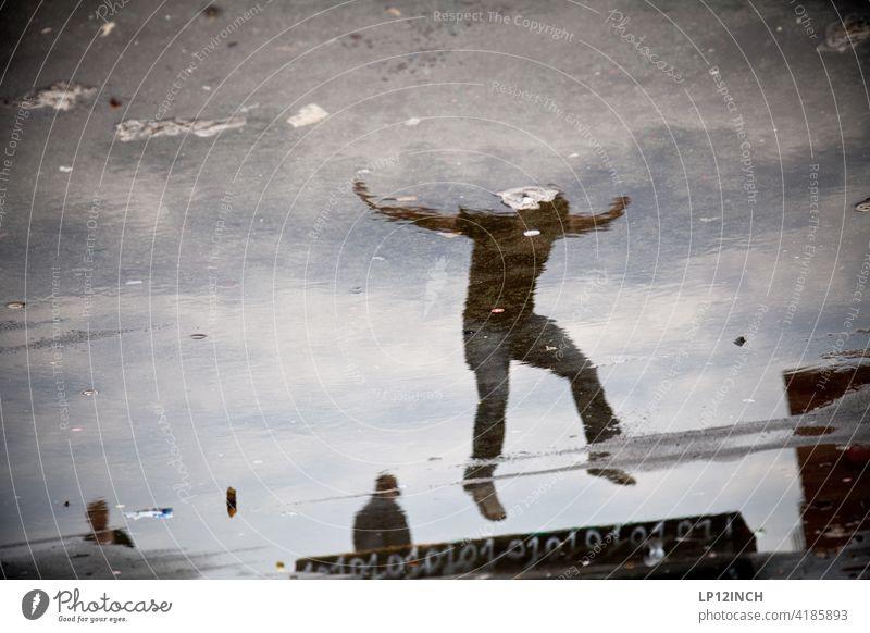 Ein Mann landet in der Pfütze Männer Reflexion & Spiegelung springen Landen Surrealismus Mensch Wasser Bodenbelag drei 3 Freude