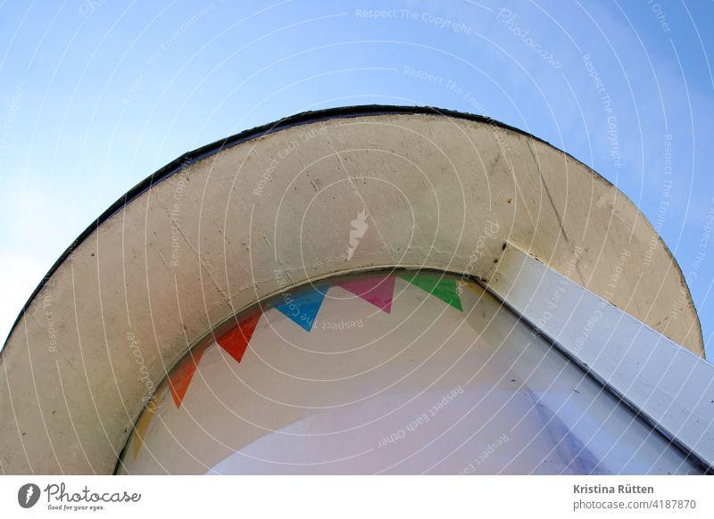 rundes dachdetail mit bunten wimpeln architektur fenster scheibe wimpelkette aufkleber fassade gebäude schräg farbig himmel fähnchen aufgeklebt deko fröhlich