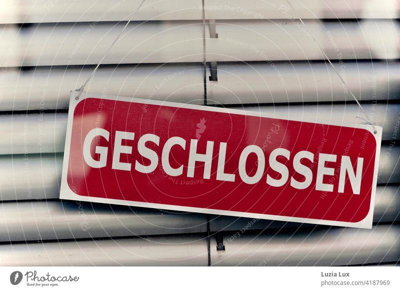 Geschlossen: dunkelrotes Schild vor heruntergelassener Jalousie in einer Ladentür. Beschilderung geschlossen Tür Hinweisschild Ladengeschäft Schriftzeichen