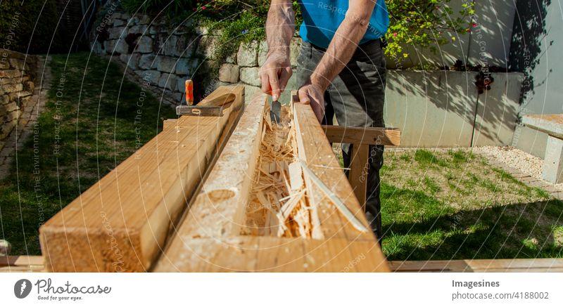 Holzarbeiten. Hohlbalken mit Meißeln aushöhlen. Schreiner verarbeitet einen Holzbalken Fräsen Werkstatt Außen Garten Farbbild horizontal Arbeitsgerät Zimmerei