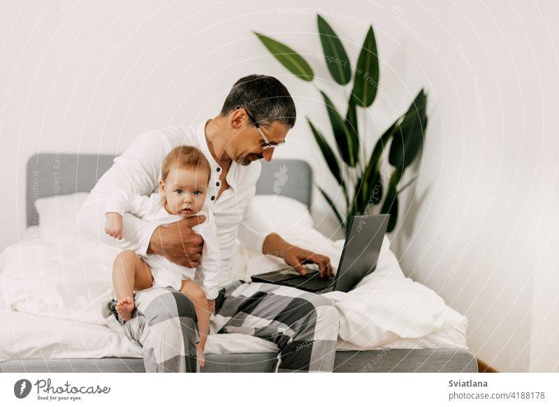 Papa sitzt auf dem Bett, arbeitet zu Hause am Laptop mit einem Baby auf dem Schoß, lächelt und schaut gemeinsam auf den Bildschirm heimwärts Internet