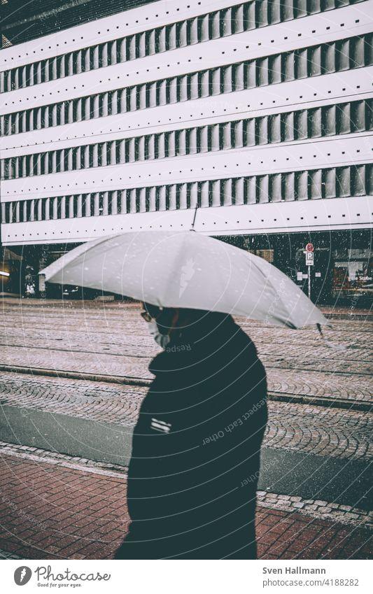 Spaziergänger im Regen mit Schirm Architektur Regenschirm Schnee Unwetter street Wetter nass regnerisch Herbst saisonbedingt im Freien regnet Wasser Großstadt