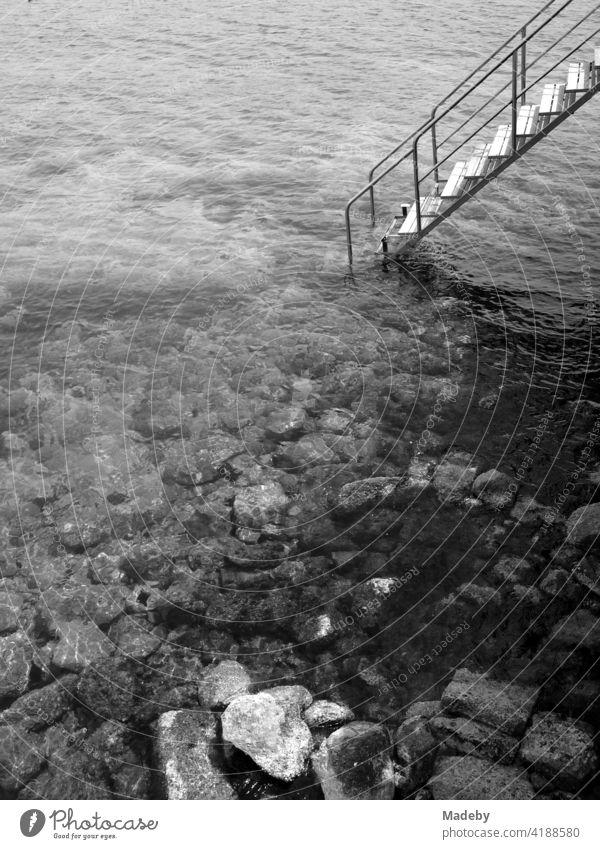 Badetreppe in der Bucht von Alacati am Ägäischen Meer in der Provinz Izmir in der Türkei, fotografiert in neorealistischem Schwarzweiß Strand Wasser Steinstrand