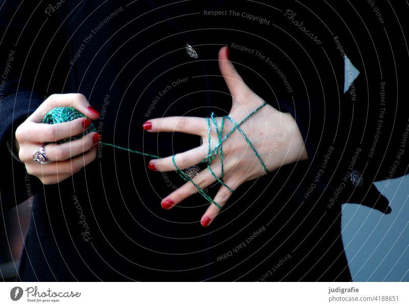 Verfänglich – Mit grüner Schnur umwickelte Hand einer jungen Frau fädeln Knoten Handarbeit Haut Lack Nähgarn Farbe Fingernagel Nagellack stricken
