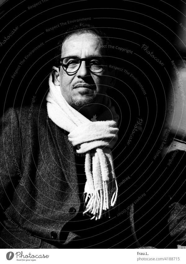 Ein Mann mit Schal Winter Brille Gesicht Porträt Blazer Jacke ernsthaft Sonnenschein