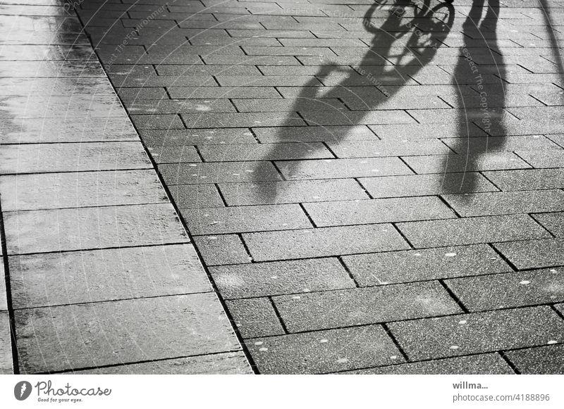Dialog einer Begegnung Personen Schatten Menschen Gespräch Treffen Fußgänger Fahrradfahrer Kommunikation schwatzen Platz Gehwegplatten Kommunizieren Fußweg