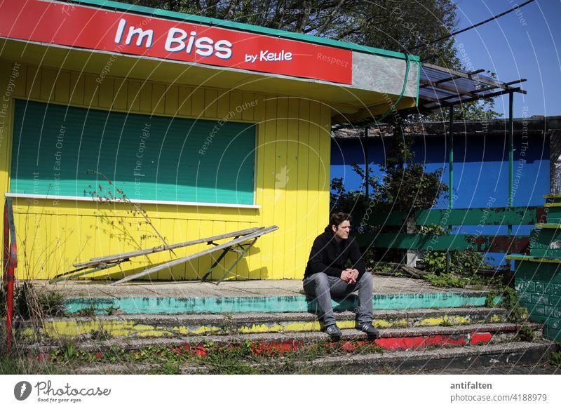 Im Biss by Keule Imbiss Imbissbude geschlossen Rolladen trist Fassade Außenaufnahme Wand Mauer alt Fenster Mann sitzen Treppe bunt runtergekommen zerfallen