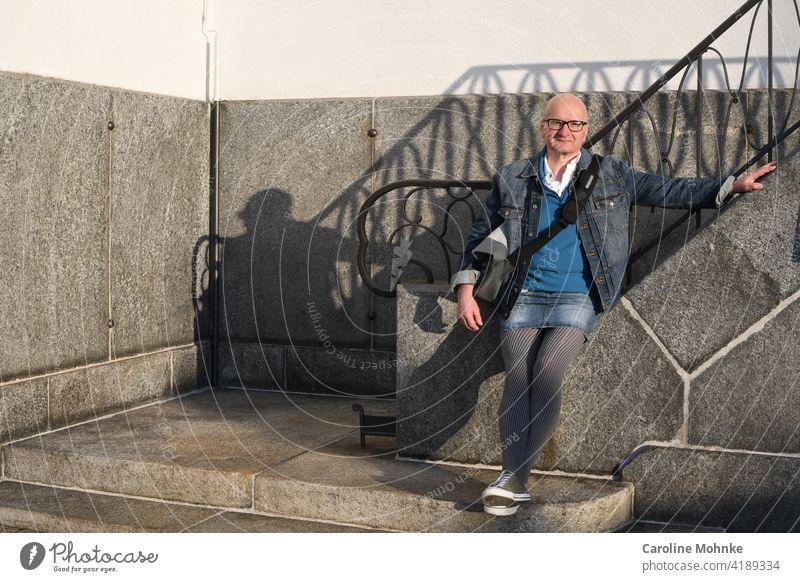 Mann in Jeansjacke, Jeansmini, Hahnentrittmuster Strumpfhose und Sneakers an einer Treppe Mode Individualist Farbfoto Außenaufnahme Tag Menschenleer modebewusst