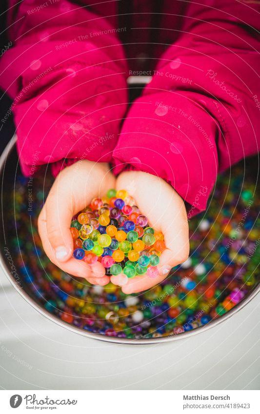 Mädchen spielt mit Wasserperlen Kind Hand Kinderhand Kinderhände Basteln matschen Spielen bunt farbenfroh Kindheit Kleinkind Finger