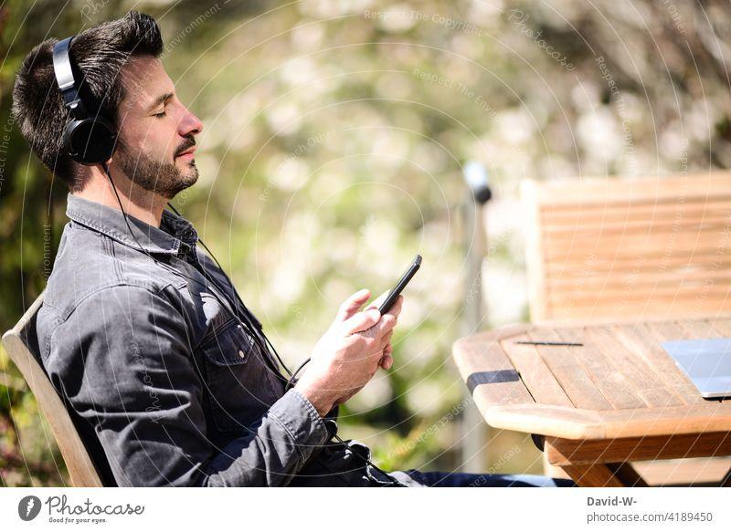 Mann hört Musik über sein Handy - Enstpannung streamen hören Kopfhörer entspannung genießen Auszeit chillen Natur Schönes Wetter Lifestyle