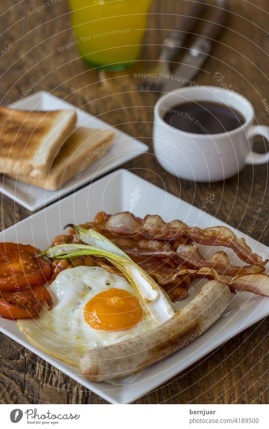 Nahaufnahme eines englischen Frühstücks Tomate Zwiebel Seite SpiegelEi Toast Speck rustikal bohne Fleisch Pilz Wurst Teller Butter Gericht traditionell morgen