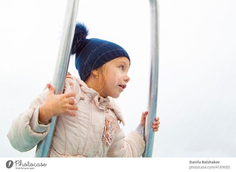 Mädchen in Herbst Kleidung dreht sich und balanciert auf modernen Metall-Karussell gehen Sie Bewegung Saison aktiv Gerät außerhalb Vorschule Pflege lustig schön