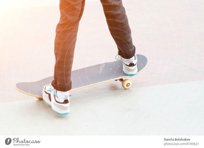 Skateboard und Beine eines Mannes, der darauf fährt, Nahaufnahme im Freien trendy altehrwürdig Hipster Person üben Training Sommer trainiert. Genuss Gefahr