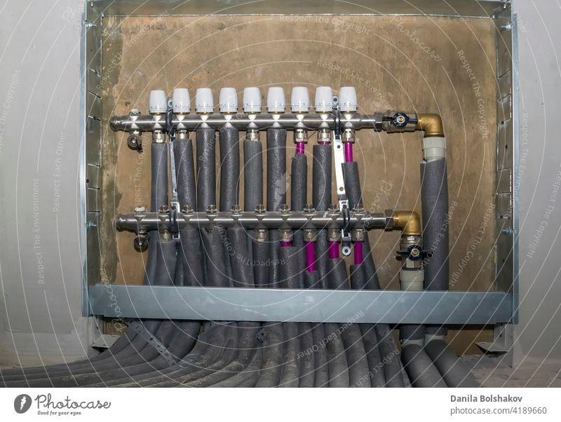 Kollektorkasten mit Kamm und Hähnen an Rohren des angeschlossenen Heizsystems Anschluss intern thermisch strahlend wohnbedingt pipleline Heizungsanlage