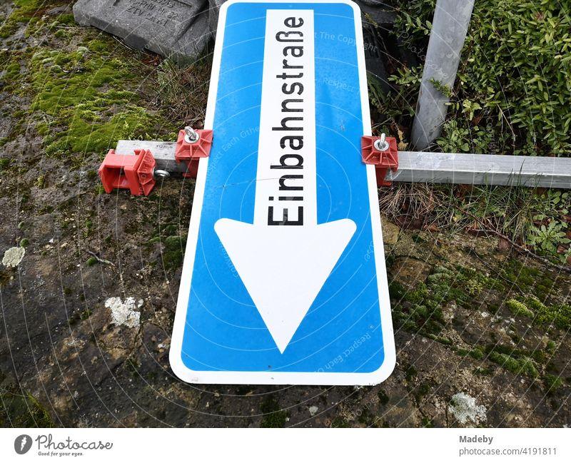 Blaues Verkehrszeichen mit der Aufschrift Einbahnstraße auf dem Boden liegend an einer Baustelle in Oerlinghausen bei Bielefeld am Hermannsweg im Teutoburger Wald in Ostwestfalen-Lippe