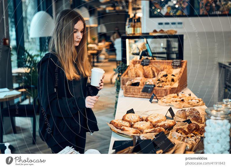 Frau hält Tasse mit Kaffee Blick auf Gebäck, Brötchen, Kuchen und Kekse und wartet auf die Bestellung. Mädchen kauft ein süßes Essen und heißes Getränk zum Mitnehmen. Junge Frau mit einer Pause beim Einkaufen in einem Café