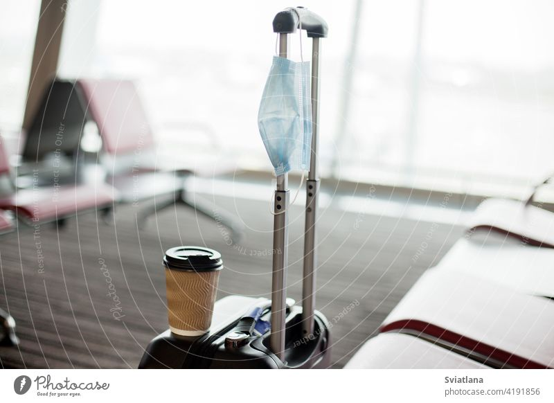 Neben den Sitzen in einem leeren Flughafen steht ein Koffer, darauf steht ein Glas Kaffee, daran hängt eine medizinische Schutzmaske. Coronavirus, soziale Distanz, Isolation
