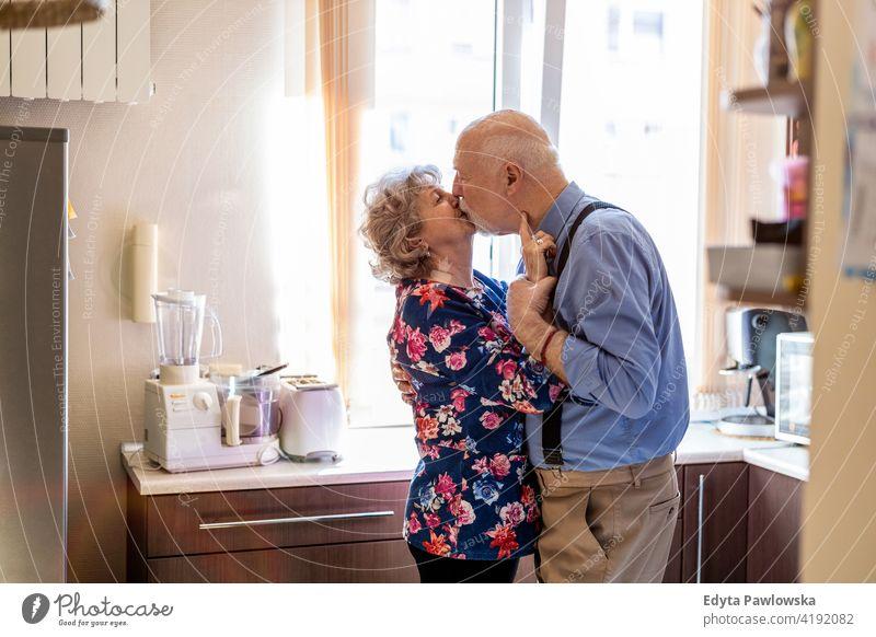 Glückliches Seniorenpaar, das sich in der Küche küsst echte Menschen offen Frau reif männlich Mann Paar Zusammensein Liebe Bonden Kaukasier älter heimwärts Haus
