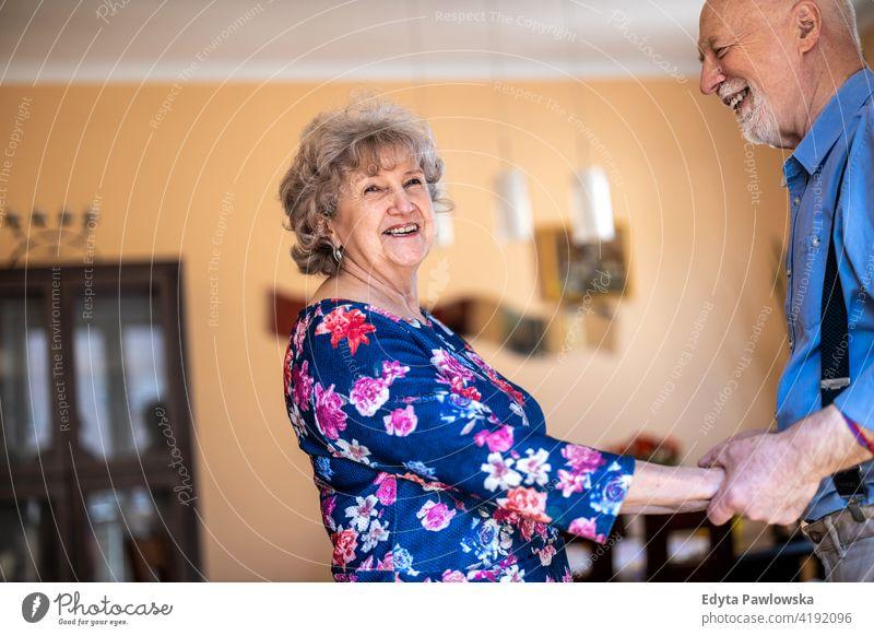 Glückliches Seniorenpaar tanzt zusammen zu Hause echte Menschen offen Frau reif männlich Mann Paar Zusammensein Liebe Bonden Kaukasier älter heimwärts alt