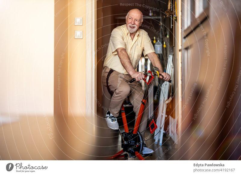 Senior Mann mit Heimtrainer zu Hause Fahrrad Zyklus stationäres Fahrrad Übung Spinnrad Fitness Sport Hobby Gesundheit aktiv ausarbeitend anstrengen Therapie