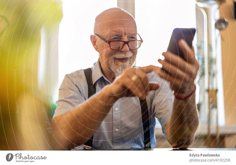 Aufnahme eines älteren Mannes, der ein Mobiltelefon zu Hause benutzt Smartphone Handy Technologie Technik & Technologie Mitteilung online modern Anschluss