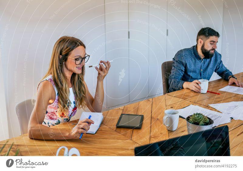 Büroangestellter, der mit einem Mobiltelefon mit Lautsprecher spricht Geschäftsfrau sprechender Lautsprecher Handy Mitarbeiter stören Mobile Gespräch Lächeln