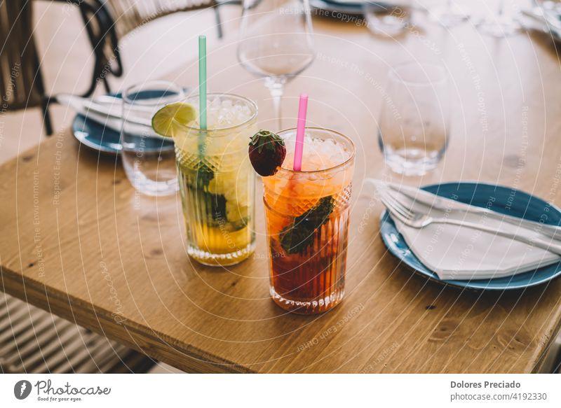 Zwei Mojito-Cocktails mit gealtertem Rum, Minze und verschiedenen Früchten. Einer mit Erdbeere und der andere mit Passionsfrucht Schnaps Caipirinha rot funkelnd