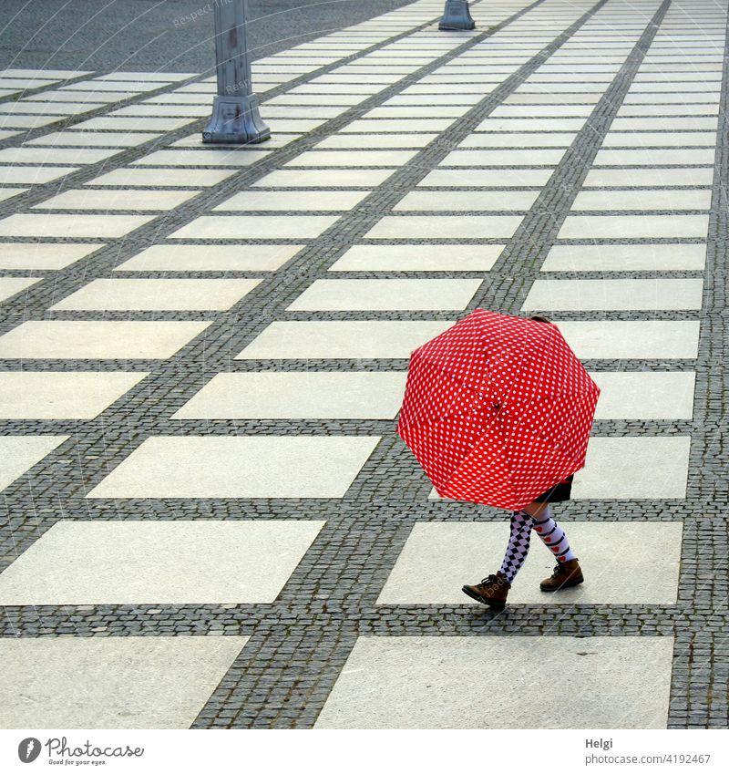 Frau mit bunten Strümpfen hinter einem rot-weiß gepunkteten Regenschirm auf einem großen Platz mit grafischer Pflasterung Mensch Beine Schuhe gemustert