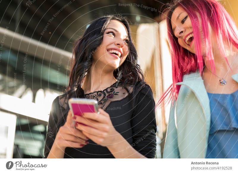 Lächelnde Frauen in der Stadt mit Smartphone lachend zusammen jung attraktiv 20s Freude Menschen Person Jugend urban hübsch hübsche Menschen im Freien Großstadt