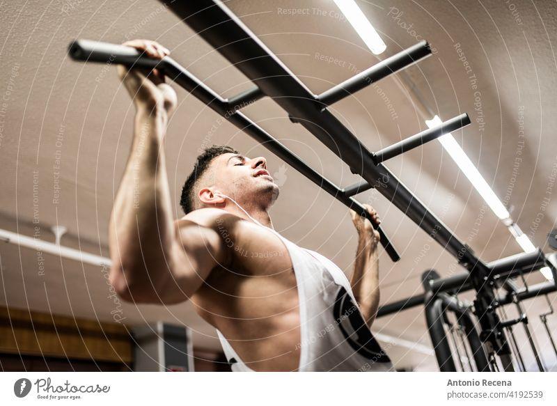 Mann macht Klimmzüge mit Langhantel in einer Turnhalle 20s 25-29 Jahre aktiv Athlet sportlich Körper Kaukasier Opferbereitschaft Tatkraft Übung trainiert.