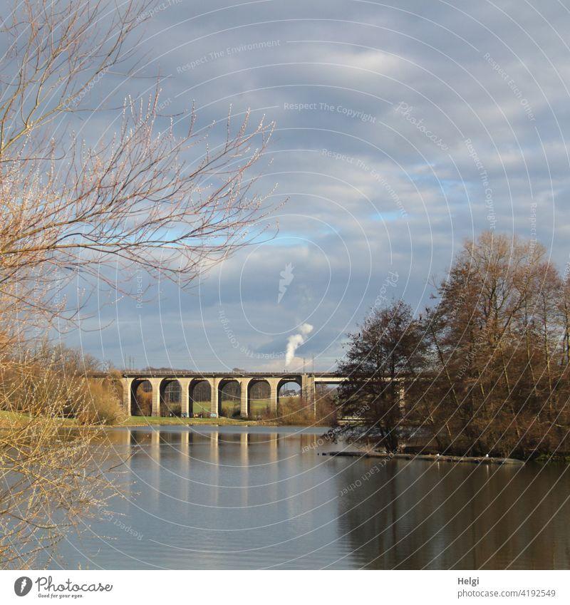 Viadukt am See mit Spiegelung, im Hintergrund hohe rauchende Schornsteine Brücke Obersee Bielefeld Rauch Seeufer Baum Strauch Himmel Wolken Landschaft Natur