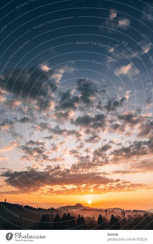 Sonnenaufgang mit Wölkchen auf dem Land Himmel Wolken Gegenlicht blau orange gelb Berg Hügel Horizont schön Neubeginn Start Tag Morgen früh morgens Weite