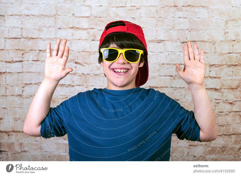 glücklicher und lächelnder Junge mit Mütze und Sonnenbrille zeigt Handflächen Accessoire Brille Lächeln Kind Glück Fröhlichkeit Verschlussdeckel Kaukasier