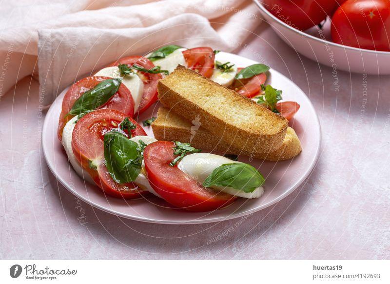 Hausgemachter italienischer Caprese-Salat mit geschnittenen Tomaten, Mozzarella-Käse, Basilikum und Olivenöl Salatbeilage Lebensmittel mediterran Italienisch