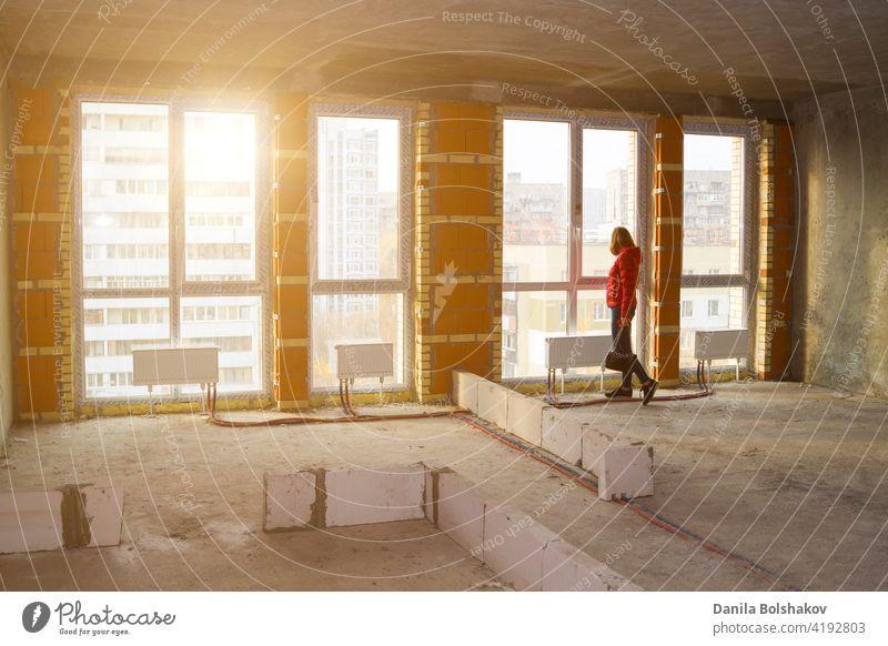 Mädchen schauen aus Fenstern von riesigen neuen Luxus moderne Wohnung mit Panoramafenstern in Wohngebäude im Bau Glas Rahmen Türen Kunststoff renovieren