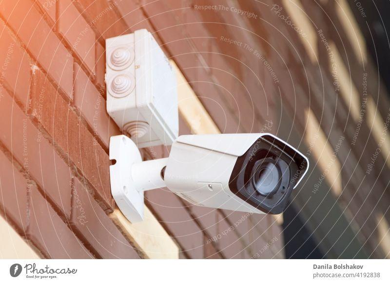 Closed-Circuit-TV-Kamera an einer Ziegelwand montiert. CCTV-Sicherheitskamera im Außenbereich. Aufsicht Ermahnung Prävention Erkennung inspizieren Detektor